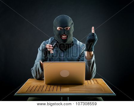 Hacker holding stolen credit card and showing middle finger