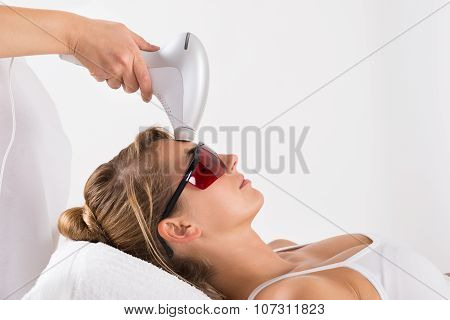 Closeup of young woman undergoing laser treatment at salon poster