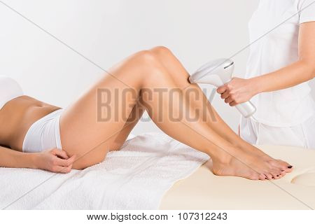 Midsection Of Beautician Using Laser Machine On Customer's Leg