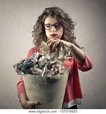 Bored woman holding a bin full of trash