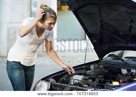 Confused Woman Looking At Broken Down Car Engine