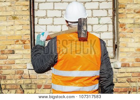 Construction worker with a sledgehammer at brick wall