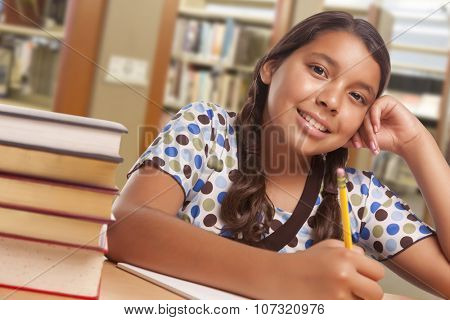 Happy Hispanic Girl Student with Pencil and Books Studying in Library.