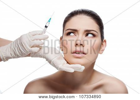 Scared girl looking at syringe