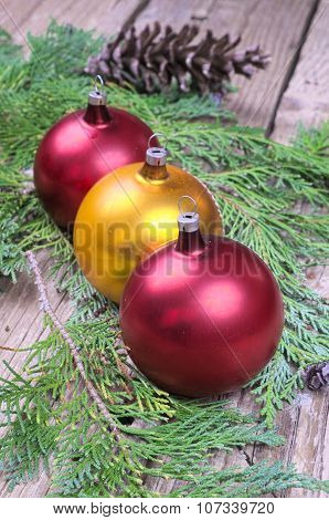 Three Colored Christmas Balls On Pine Needles On A Wooden Table