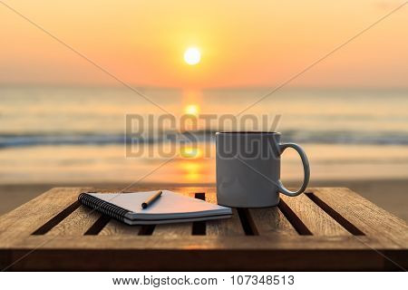 Coffee cup and book on wood table at sunset beach