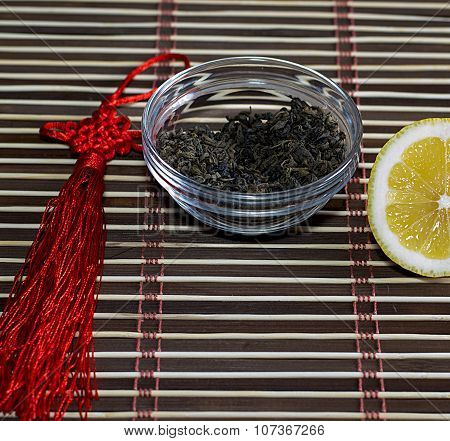 Saucer With Leaves Of Tea And The Cut Lemon On A Rug