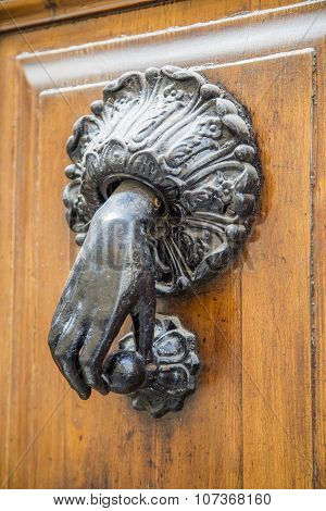 Close view of the door knocker in a form of a hand