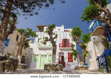 Small square of at Mykonos town with clear blue sky and trees, Greece