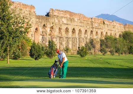 ROME, ITALY - SEPTEMBER 2015: Unidentified man playing golf at the golf course next to the Ancient Roman Aqueduct in  Parco degli Acquedotti. Famous Aqua Claudia Aqueduct is around 2000 years old.
