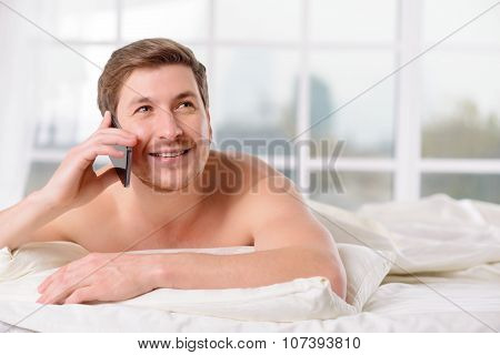 Guy talks on the phone while lying in bed.