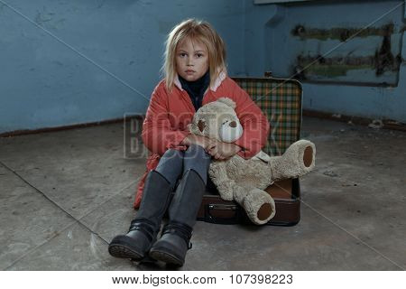 Lonely girl sitting on the suitcase