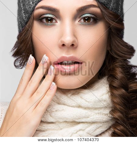 Beautiful girl with a gentle make-up, design manicure and winter gray knit cap. Warm winter image. Beauty face. Picture taken in the studio. poster
