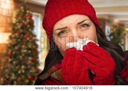 Sick Mixed Race Woman Blowing Her Sore Nose With Tissue In Christmas Setting.