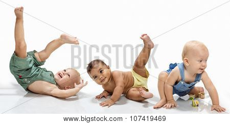 Multiethnic babies dancing on light background