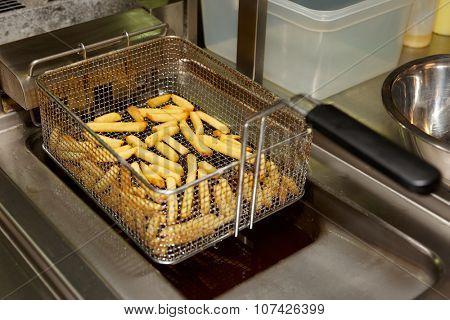 French fries in deep fryer, restaurant kitchen