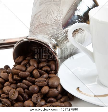 Coffee grains in a white cup and disseminated about a coffee pot on a light background. Close up.