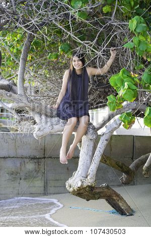 Biracial Teen Girl Sitting On Tree Branch On Beach