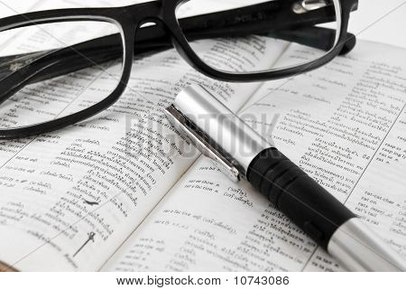 Closeup Of Dictionary And Glasses With Pen