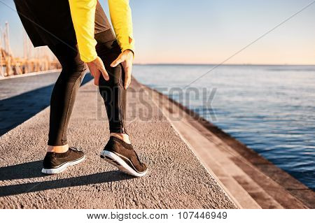 Muscle injury - Athlete running clutching calf muscle after spraining it while out jogging on the beach near ocean. Sports injury concept with running man outside poster