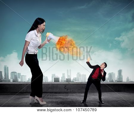 Big boss yelling to her employee with megaphone on fire. Work pressure concept poster