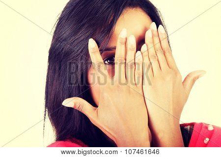 Shy woman peeking through covered face