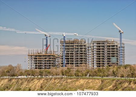 Construction cranes and buildings on construction site