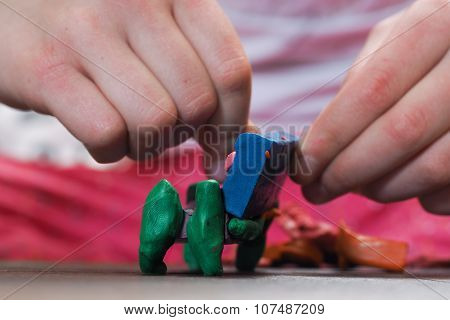 Small child sculpts from clay bed