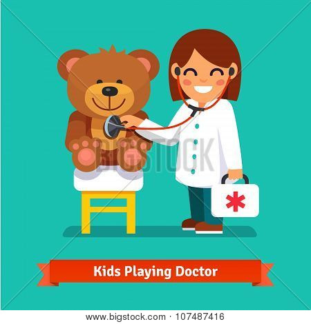 Small girl playing a doctor with teddy bear toy