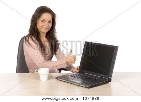 Young Woman At The Desk With Laptop Showing Ok