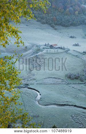 Cabin In Frozen Grass On Hill