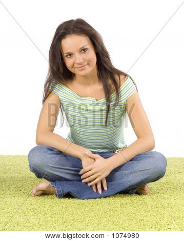 Young Woman Sitting On The Green Carpet