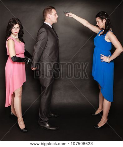 Scene of violence with firearm between men and women. Elegant lady holding gun aiming at man in suit on black and grey background in studio. poster