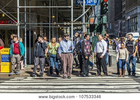 People Crossing A Street At A Pedestrian Crossing In New York