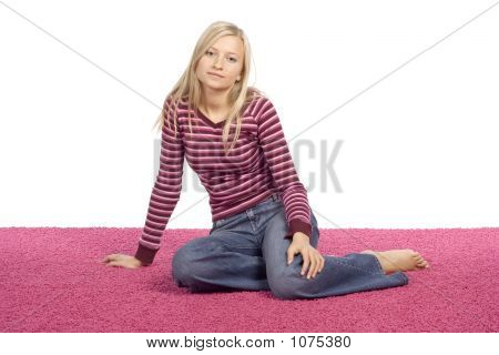 Young Blonde Woman Sitting On The Pink Carpet