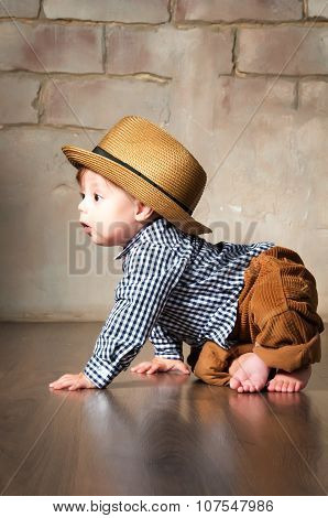 Llittle Boy In Retro Hat And Corduroy Trousers Learning To Crawl On Floor On All Fours