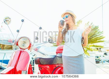 Happy young trendy woman drinking takeaway coffee near her red moped on the waterfront in the morning poster