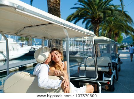 Attractive young couple driving electric car on the marina on a luxury waterfront poster