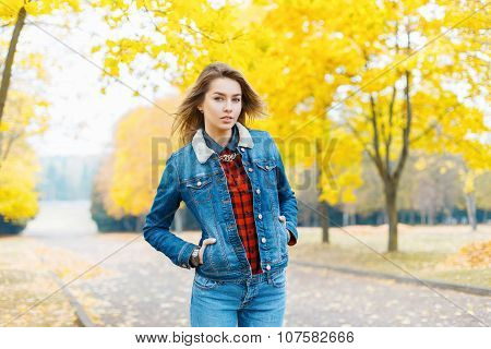 Pretty Girl In A Denim Jacket And Jeans On The Background Of Yellow Foliage, A Beautiful Fall Day