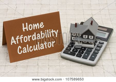 Home Mortgage Affordability Calculator, A Gray House, Brown Card And Calculator On Stone Background