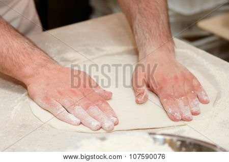 Chef is cooking pizza, forming dough poster