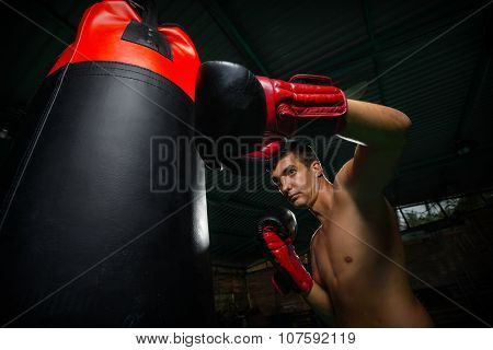 Fighter Practicing Some Kicks With Punching Bag - A Man With A Tattoo Boxing On dark Background