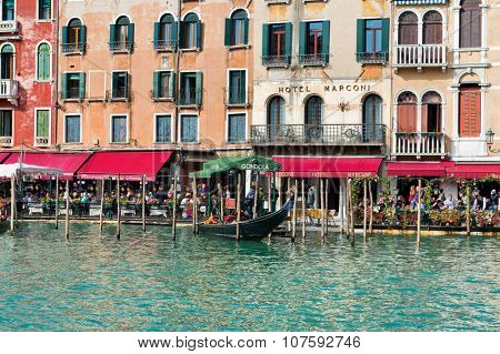 VENICE, ITALY - 17 OCTOBER 2015: Colorful open-air restaurants with red canopies in front of the Hotel Marconi on the Grand Canal, Venice in the region of the Rialto Bridge. October 17 2015.