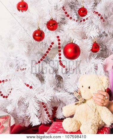 Girl Hugging Teddy Bear near christmas tree