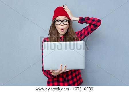 Portrait of a funny woman holding laptop computer and looking at camera over gray background