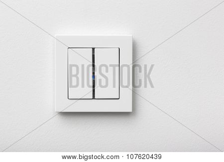 Modern light switch in the frame on white wall
