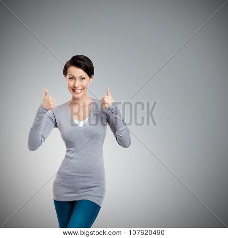 Pretty girl gives thumb up with two hands, isolated on grey