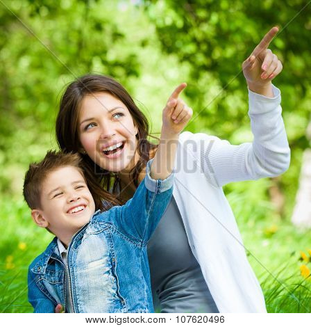 Mother and her son with book sitting on green grass pointing hand gesture in park. Concept of happy family relations and carefree leisure time
