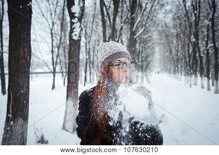 Beauty Winter Girl Blowing Snow in frosty winter Park. Flying Snowflakes. Joyful Beauty young redhead woman Having Fun in Winter Park poster