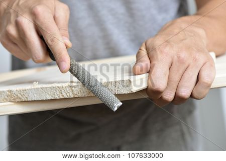 closeup of a young caucasian man filing a wooden board with a rasp